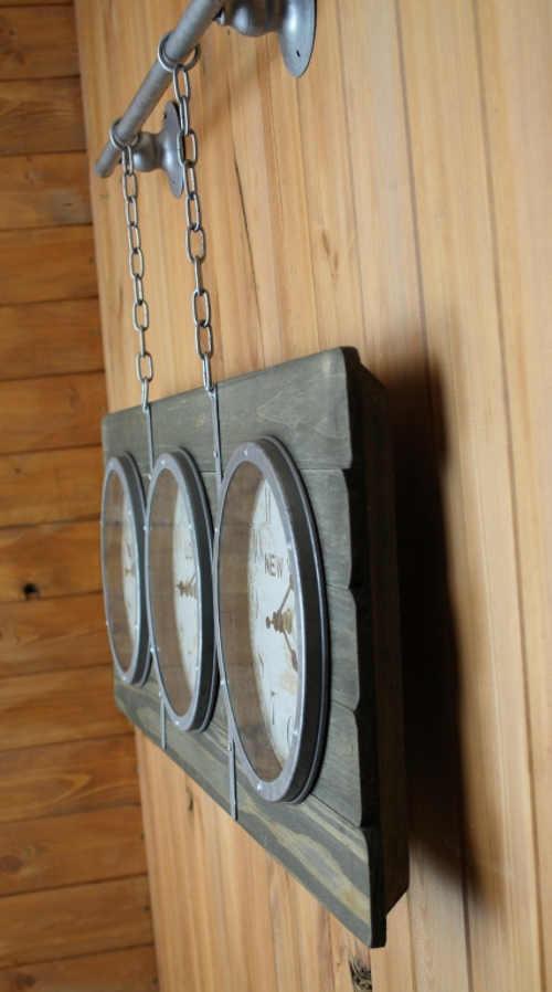 Velké dřevěné nástěnné hodiny zavěšené na kovovém řetízku